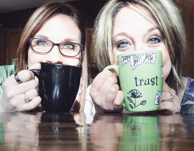 Two women with coffee cups. One black cup and one green cup that says trust