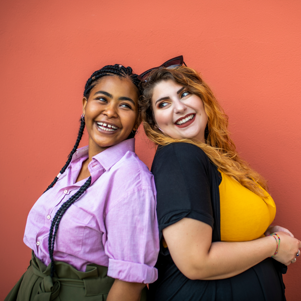 Black woman in a lavendar shirt and caucasian woman in a yellow shirt with a blue cardigan in front of a pink wall