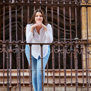 Woman with dark hair on balcony wearing a white button down shirt and jeans