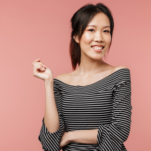 Asian Woman with a black and white striped shirt on a pink background