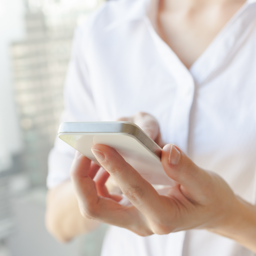 Woman in a white shirt with an iphone