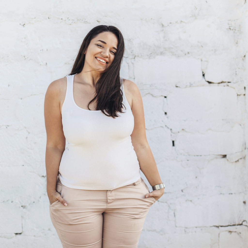 Woman with large bust in a white tank top and light pink jeans in front of a white brick wall.