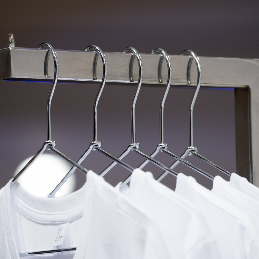 Gray background with multiple white t-shirts on hangers