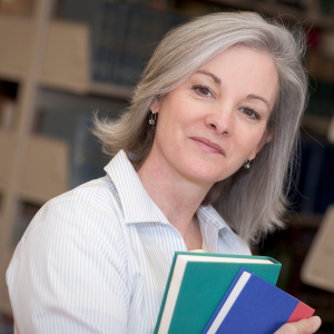 Woman with silver hair in a library carrying books
