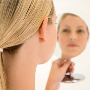 A woman with blonde hair is looking at herself in a hand held mirror.