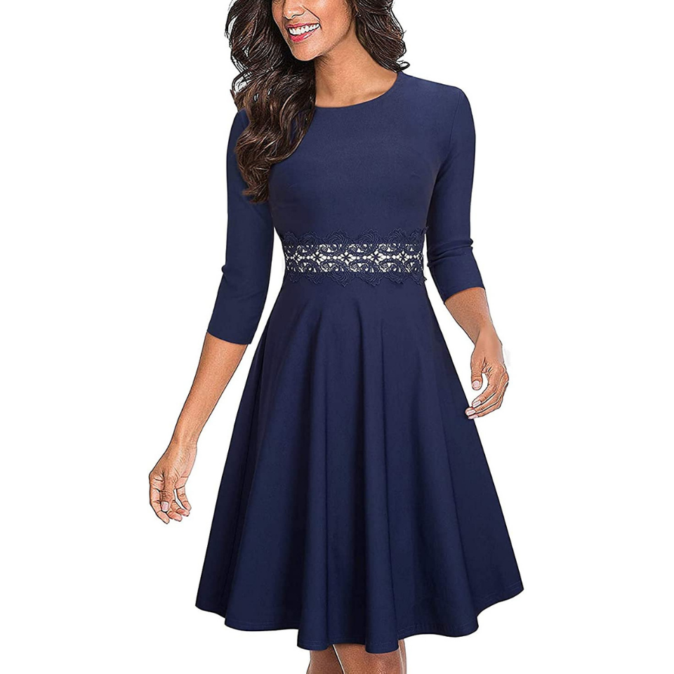 Woman in navy blue a-line dress against a white background
