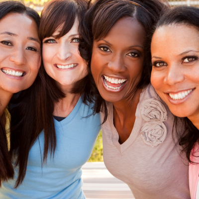 A group of four woman standing close to each other smiling
